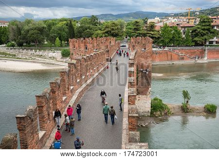 VERONA ITALY - MAY 1 2016: The Ponte Pietra (Stone Bridge) once known as the Pons Marmoreus is a Roman arch bridge crossing the Adige River in Verona Italy. The bridge was completed in 100 BC