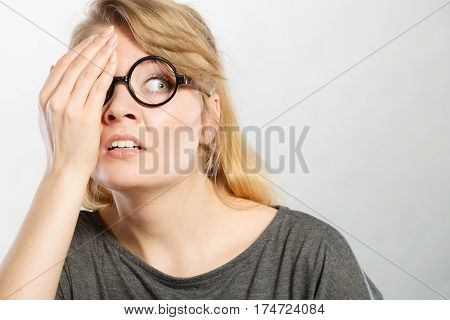Social communication shame foolishness behavior concept.Teen girl showign cringe. Young blonde lady wearing glasses making facepalm gesture.