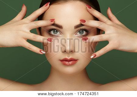 Beauty brunette woman with perfect makeup. Glamour girl. Red lips and nails. Perfect eyebrows. Skin care foundation. Beauty girls face isolated on green background. Fashion photo