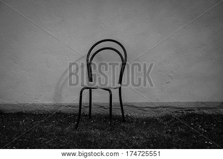 Old chair in front of house loneliness deserted sad black symbolic poor poverty