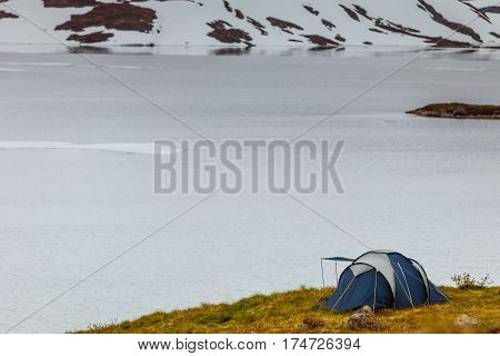 Camping with tent on snowfield with view on snow capped mountains and frozen lake in Norway.