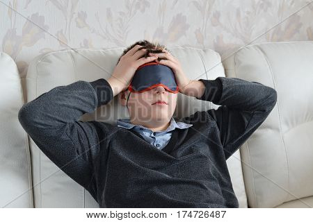 A teenager with a headache in the mask for sleep