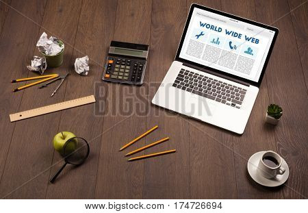Laptop computer on wooden desk with office suplies