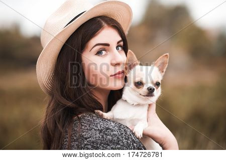 Beautiful girl 20-24 year old holding chihuahua puppy outdoors. Looking at camera.