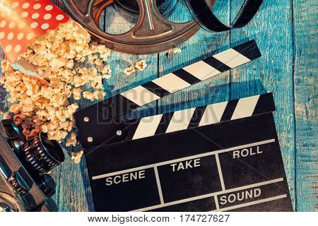 Film camera chalkboard , movie camera, roll and popcorn on wooden planks.