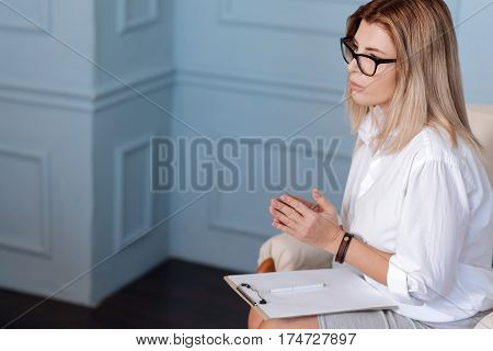 Keep calm. Serious blonde female wearing white blouse holding white paper sheet on her knees while keeping hands together