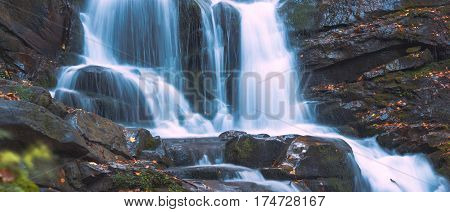 Waterfall in the Carpathian mountains. Blue clean fresh water with motion blur