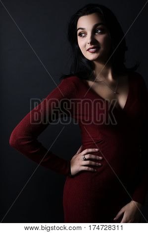 Beautiful latina wearing a red dress over a red background