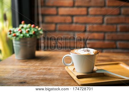 A stylish modern café with wooden tables and a brick wall. Cup of hot coffee on wooden table.