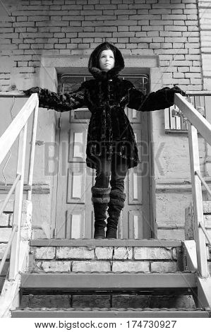 Stylish fashion brunette girl in black coat, posing on the stairs. Beauty girl in stylish coat. Model looking at camera. Fashion look.