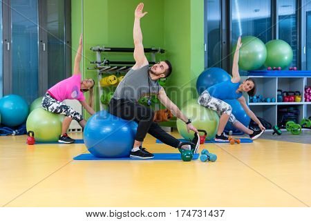 Portrait of happy group exercising on Swiss ball.