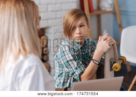 Just listen to me. Cool teenager with stylish haircut wearing fitness bracelet on right hand putting his both hands on skateboard while turning his head on female