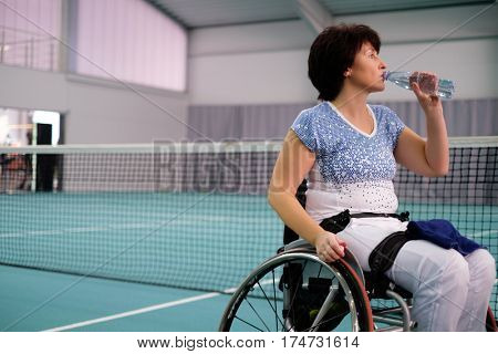 Tired disabled mature woman on wheelchair at tennis court