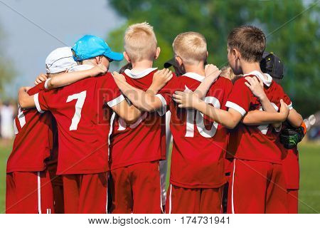 Children Soccer Team. Children Football Academy. Kids Soccer Players in Red Shirts Standing Together on the Pitch. Youth Soccer Motivational Speech. Coach Motivational Talk With Young Boys