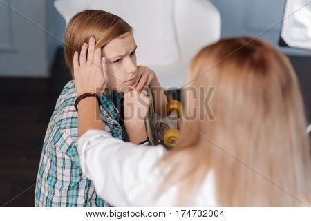 Do not give up. Sad boy wearing casual clothes wrinkling his forehead while looking on psychologist