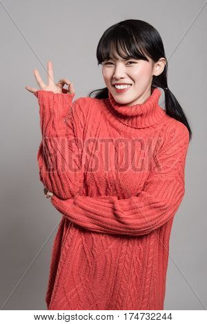 A studio portrait of a twenties Asian woman pointing at something with a finger and being happy