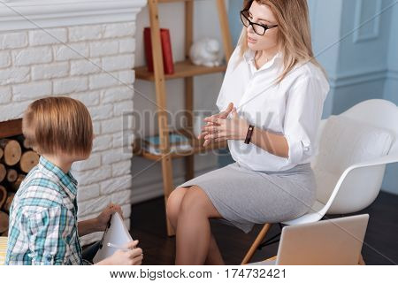 Be positive. Pretty blonde woman wearing white shirt and skirt sitting on white chair while holding her hands together