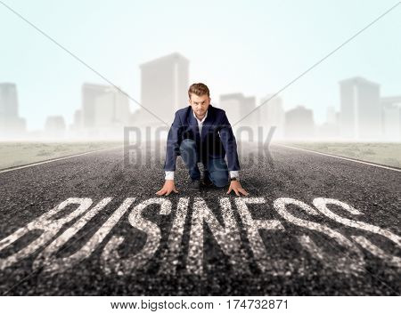 Young determined businessman kneeling before business text