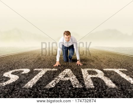 Young determined businessman kneeling at a start line
