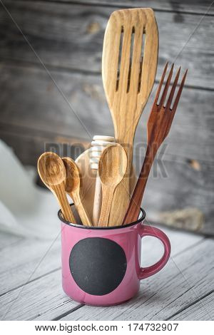 wooden utensils in a Cup with a black circle for text on wood background , concept of cooking and cuisine