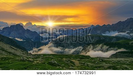 Scenic view of beautiful sunset in Dolomities with mountains covered by clouds and colorful sky