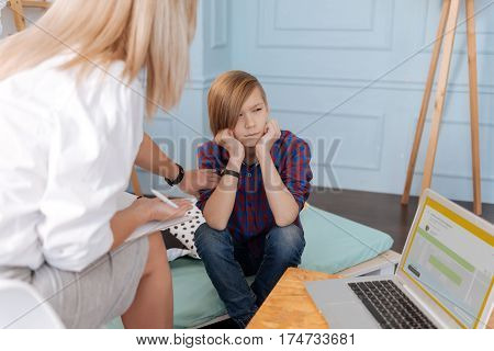 Creating plans. Thoughtful boy wearing checked shirt and jeans holding his hands on the chin looking aside