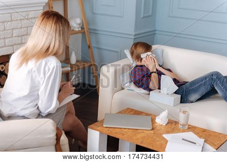 Explain it to me. Young male person lying on the sofa using wipes while crying