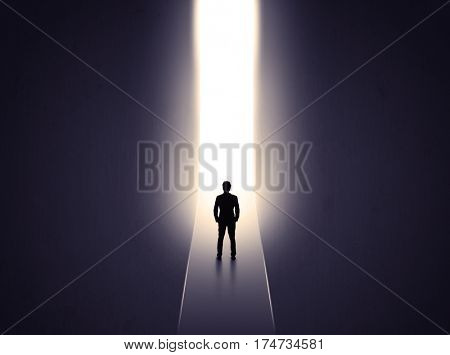 Young businessman stands in dark tunnel and looks in the glowing end
