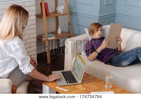 I will found it. Attentive boy lying on the white sofa holding folder in both hands while reading it