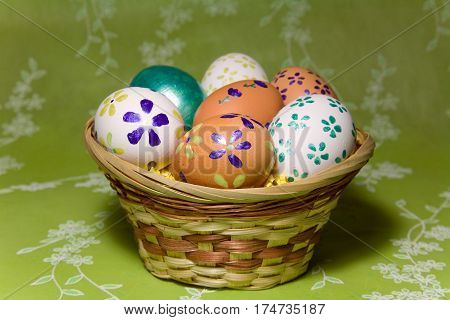 Colored easter eggs with flower laying in wood basket