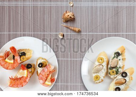 Tasty various italian sandwiches with seafood against bamboo mat background. Crostini with cheese king shrimps lemon sliced olives on white plate horizontal top view