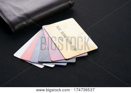 Brown leather wallet with Credit debit and discount cards on black background.