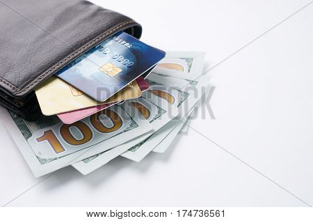 Brown leather wallet with credit debit discount cards and dollars isolated on white background with copy space.