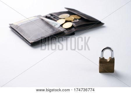 Open brown leather wallet with dollar cash coins debit credit cards inside and locked padlock.Business safety and finance protection concept