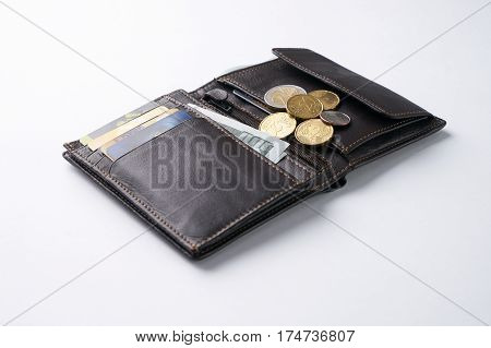 Open brown leather wallet with dollar cash coins debit credit cards isolated on white background.