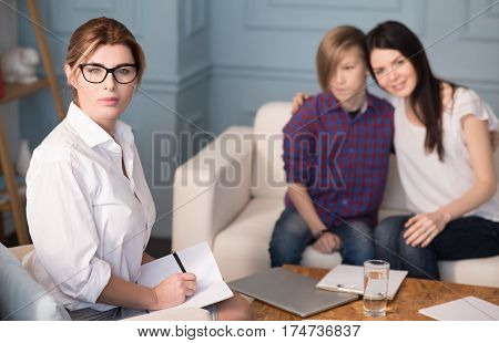 Good results. Attractive woman wearing smart clothes posing with notebook while looking straight on camera