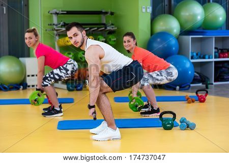 Two girl exercising at the gym with a personal trainer