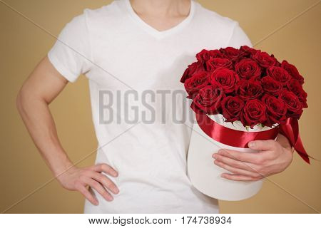 Man In White T Shirt Holding In Hand Rich Gift Bouquet Of 21 Red Roses. Composition Of Flowers In A