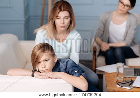 Do not touch me. Handsome boy wearing jeans costume having stylish haircut holding hands on white back of sofa while turning from mother