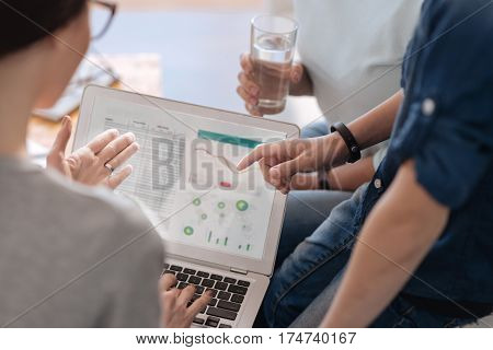 Compare it. Clever professional brunette holding computer on her knees while pointing on laptop screen sitting next to her patient