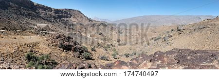 Panoramic view of a unpaved road winding through the mountains in Oman