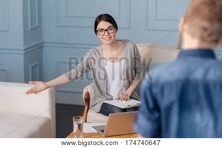Come and sit. Attentive professional wearing glasses holding folder on her knees while showing white sofa