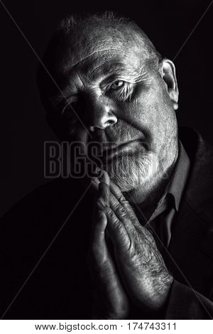 Portrait of old man over black background. Old age concept.