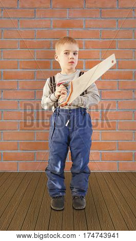 Boy child with the building tool. Is on the floor on brick wall background. The child worker the Builder. Saws with a saw. Holding the hand saw