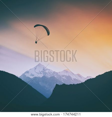 Silhouette of paraglide flying over the high caucasian mountains in a golden light of sunrise. Georgia Svaneti region.