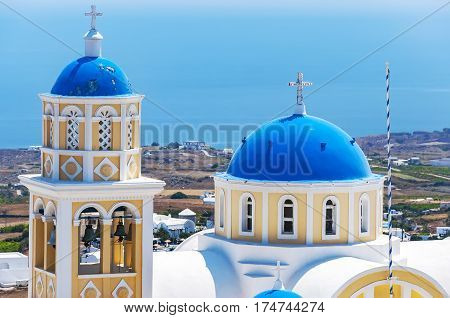 An image of the santorini capital town of fira with landmark church in the foreground.