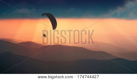 Paraglide silhouette flying over the mountains. Beautiful rays of sunset light on a foggy hills of mountain valley.