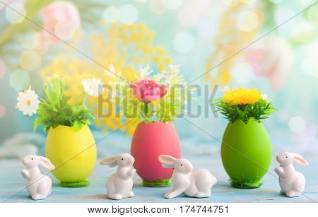 Easter decoration with spring flowers in colorful dyed eggs and white easter rabbits