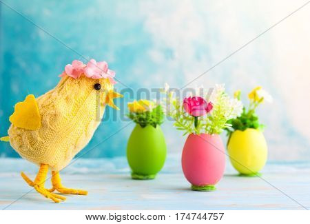 Easter decoration with funny chick and spring flower in colorful dyed eggs