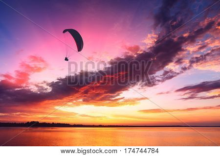 Paraglide silhouette in a light of majestic sunset flying above the sea.